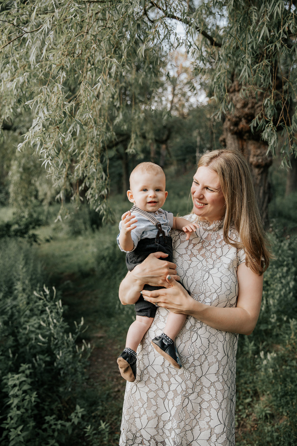 mom standing under willow tree at high park with 8 month old blonde baby boy in her arms, son smiling at camera, mother smiling at son - Markham Lifestyle Photography
