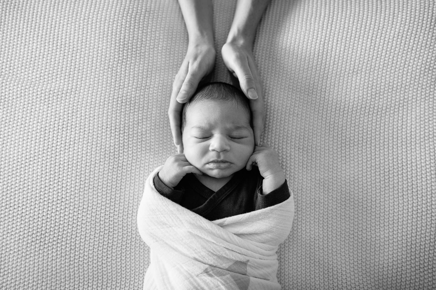 2 week old baby boy with dark hair in dark onesie wrapped in white swaddle, sleeping on bed with hands beside cheeks, mom's hands cradling son's head - Stouffville In-Home Photography