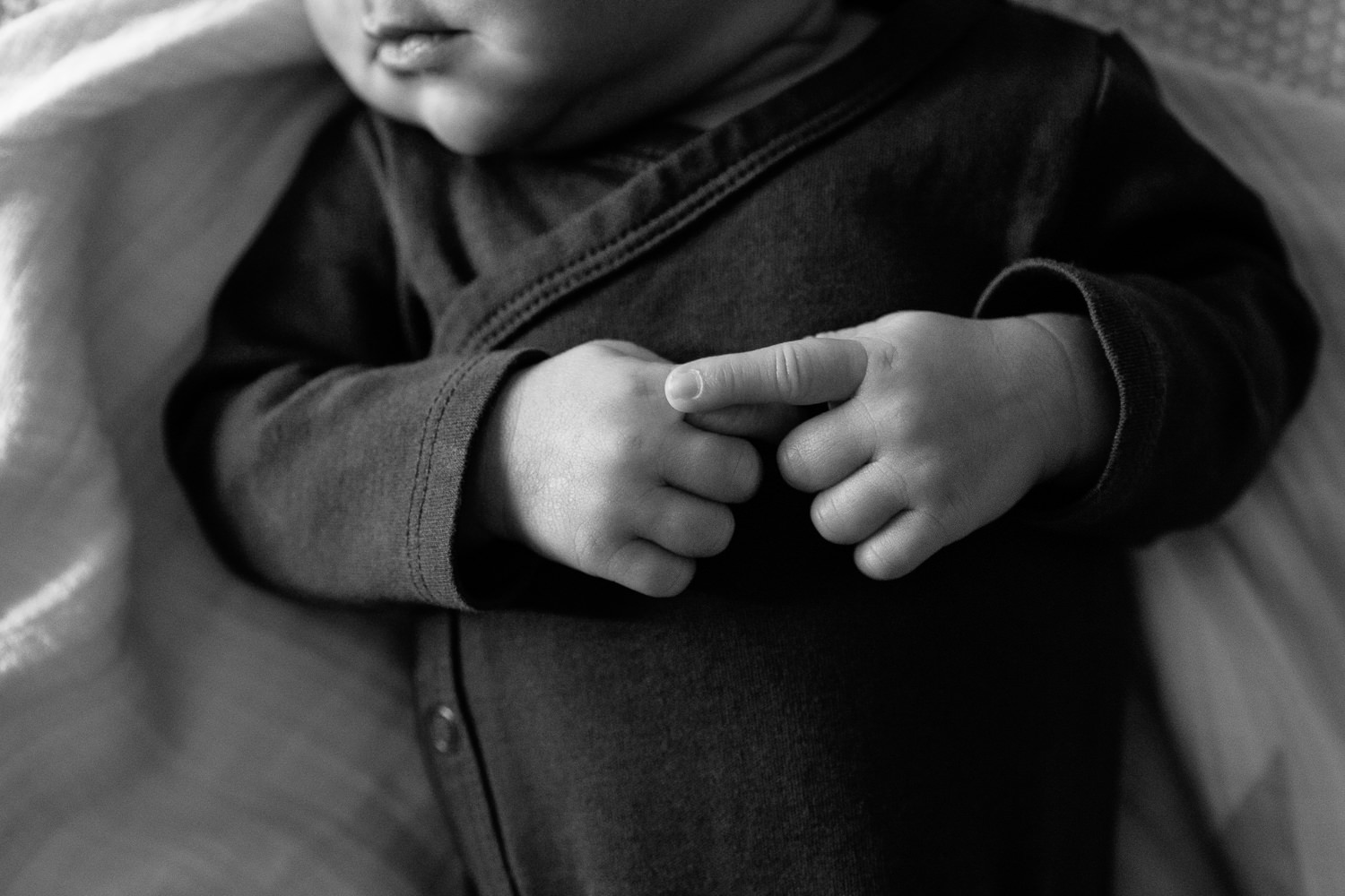 2 week old baby boy wearing dark onesie lying on bed, close up of hands clasped on chest - Barrie In-Home Photography