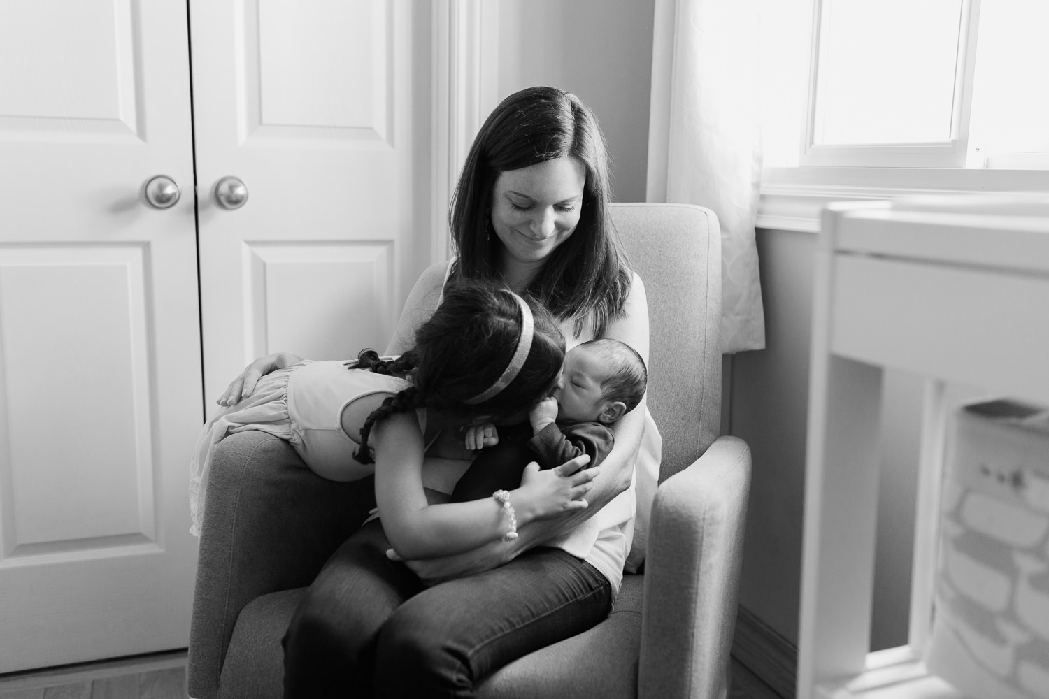 mom sitting in grey glider in neutral nursery holding 2 week old baby boy as 4 year old big sister leans over and kisses brother - York Region In-Home Photos