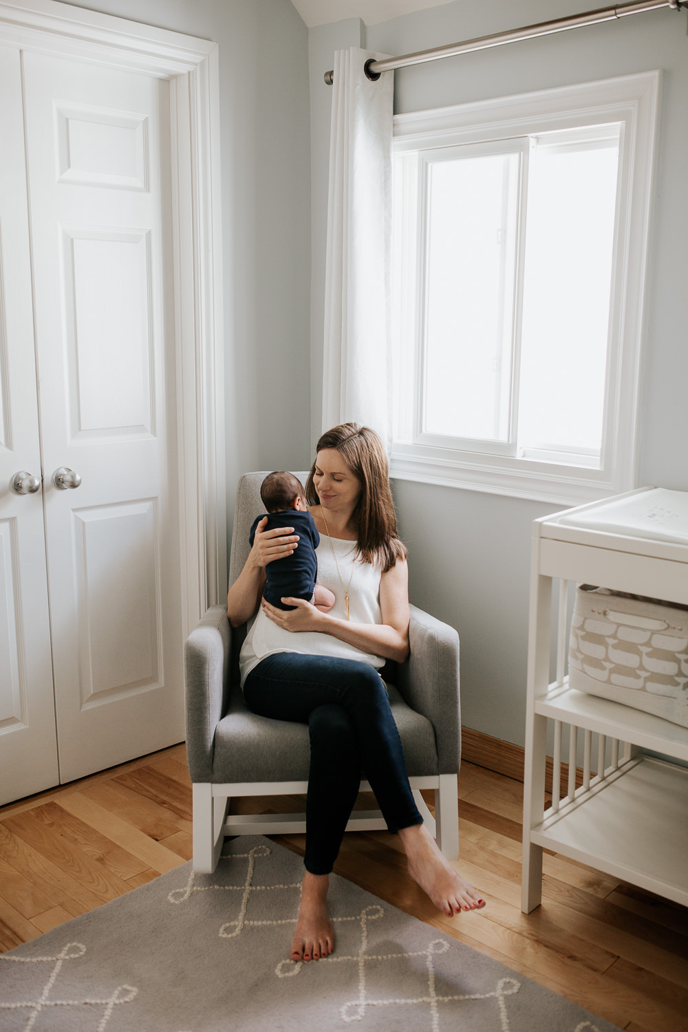 mom with long brown hair in white top and jeans sitting in grey glider in neutral nursery holding 2 week old baby boy in navy onsie with dark hair to her chest and smiling at son - Stouffville Lifestyle Photos