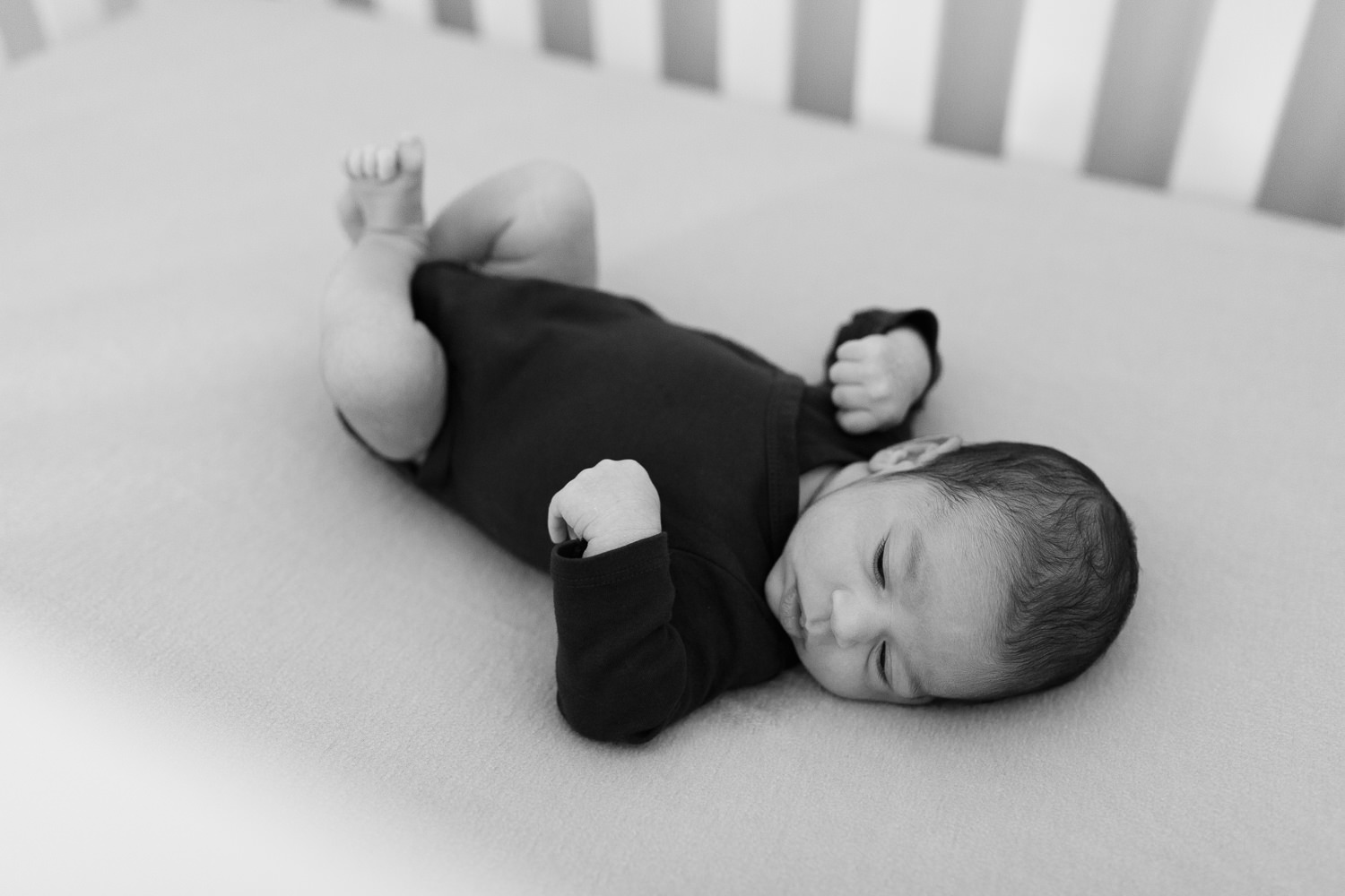 2 week old baby boy with dark brown hair lying in crib in nursery - York Region Lifestyle Photos