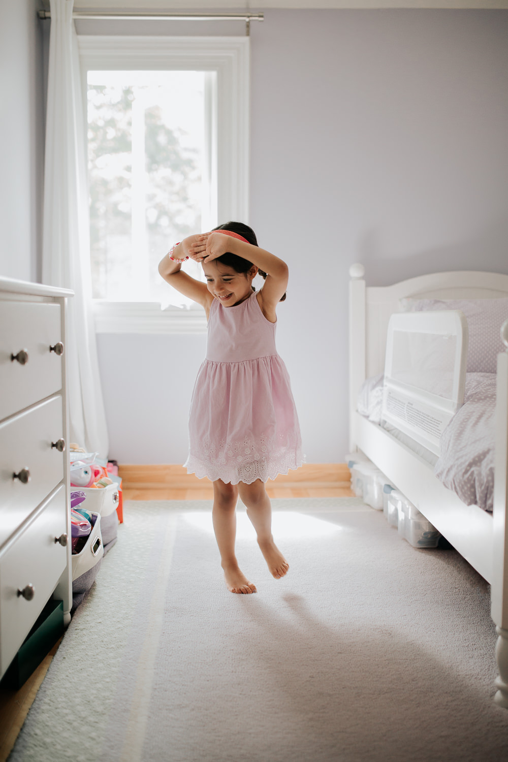 4 tear old toddler girl with dark braided pigtails in purple dress twirling like a ballerina in front of window in bedroom and smiling - Stouffville Lifestyle Photography