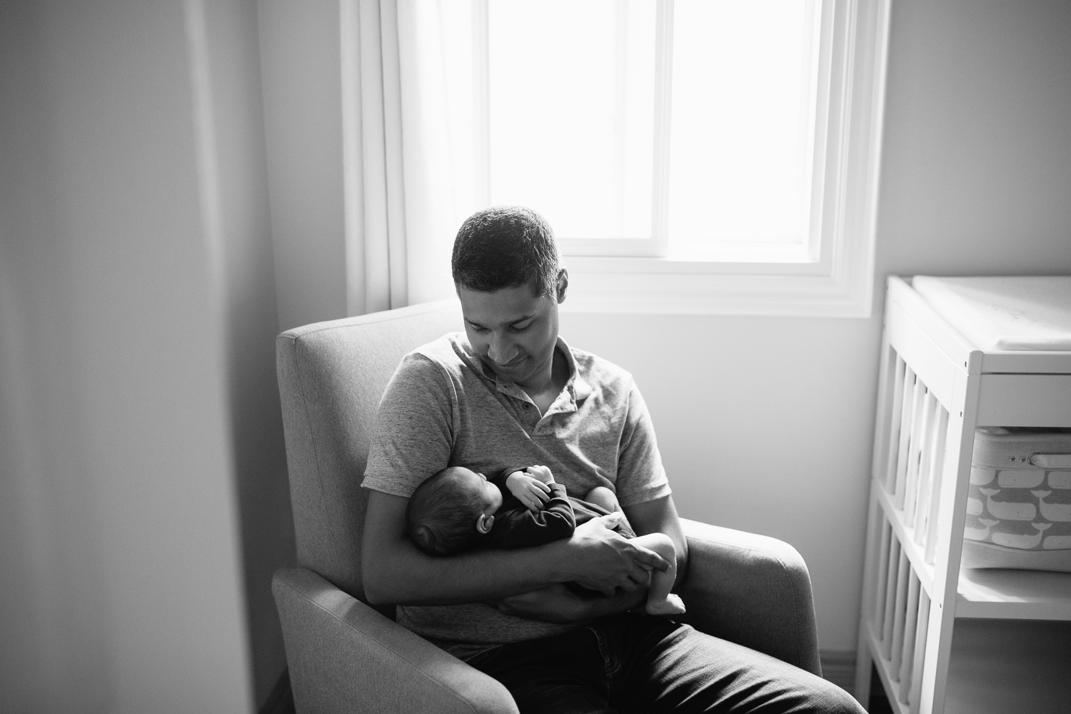 father sitting in nursery rocker holding 2 week old baby boy in navy blue onesie who is sleeping with arms crossed - York Region Lifestyle Photography