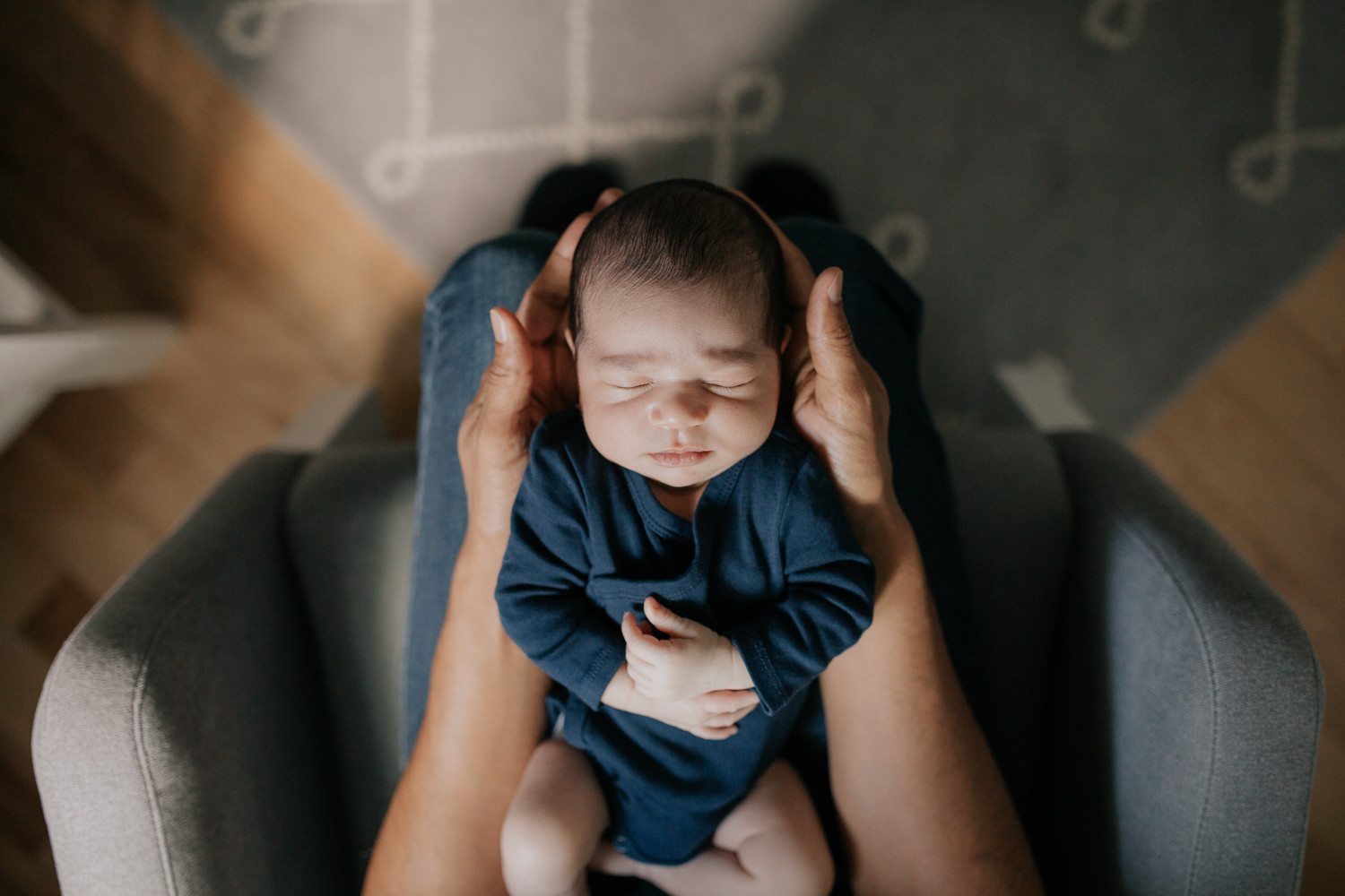 father sitting in nursery rocker holding 2 week old baby boy in navy blue onesie who is sleeping with arms crossed, shot from above - Stouffville In-Home Photography