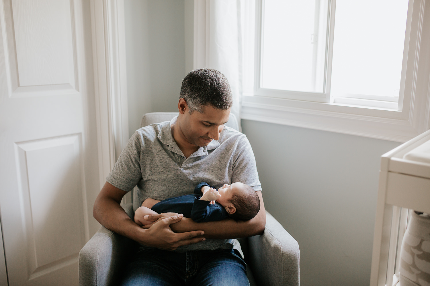 father sitting in nursery rocker holding 2 week old baby boy in navy blue onesie who is sleeping - Markham In-Home Photography