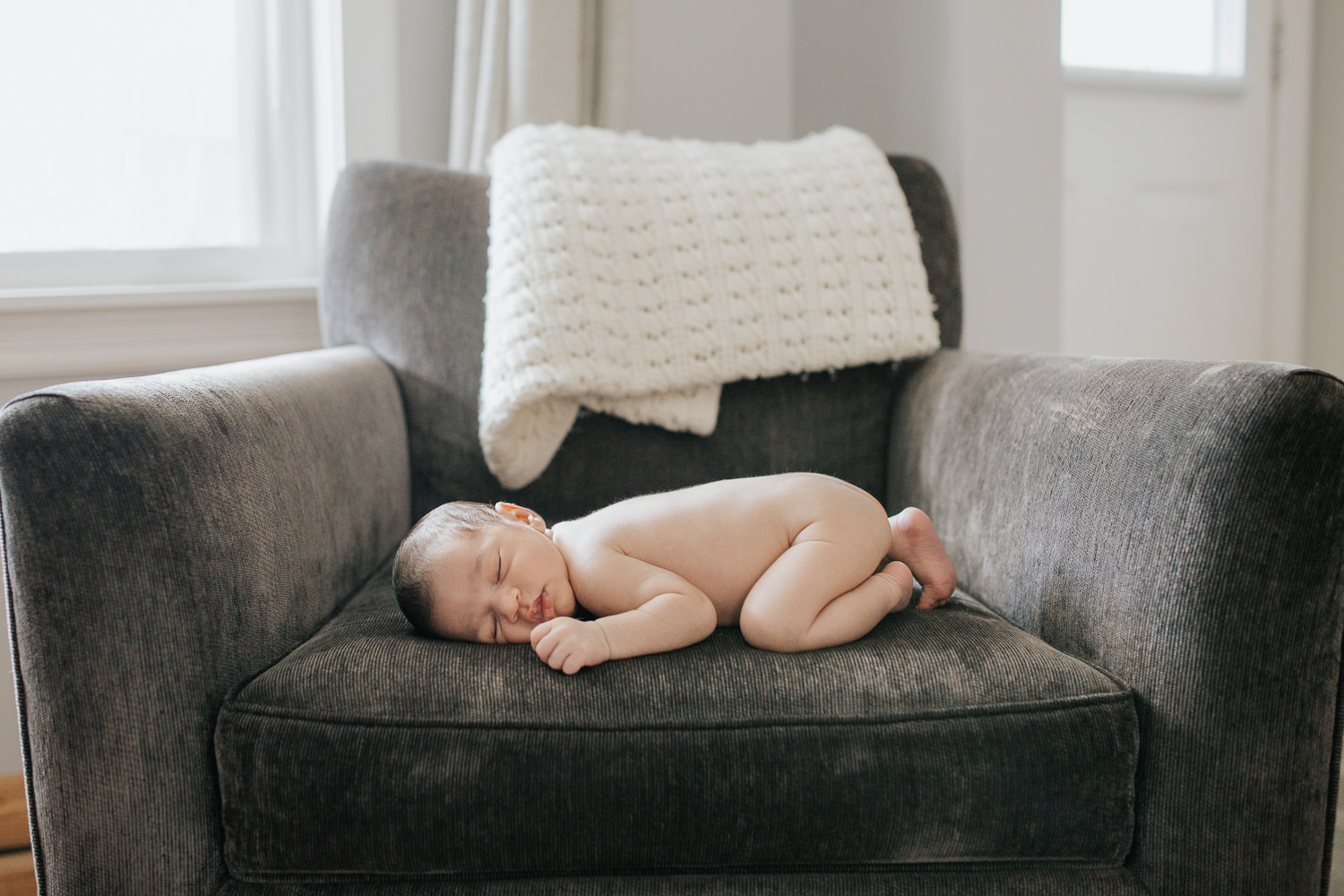 2 week old baby boy with dark hair sleeping on stomach on dark grey chair - York Region In-Home Photography