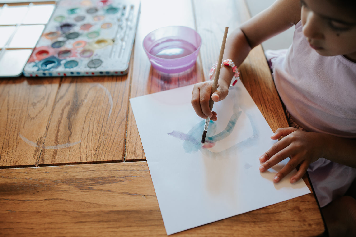 4 year old toddler girl with dark hair in pigtails wearing purple dress sitting at kitchen table painting with watercolours - Stouffville Lifestyle Photos