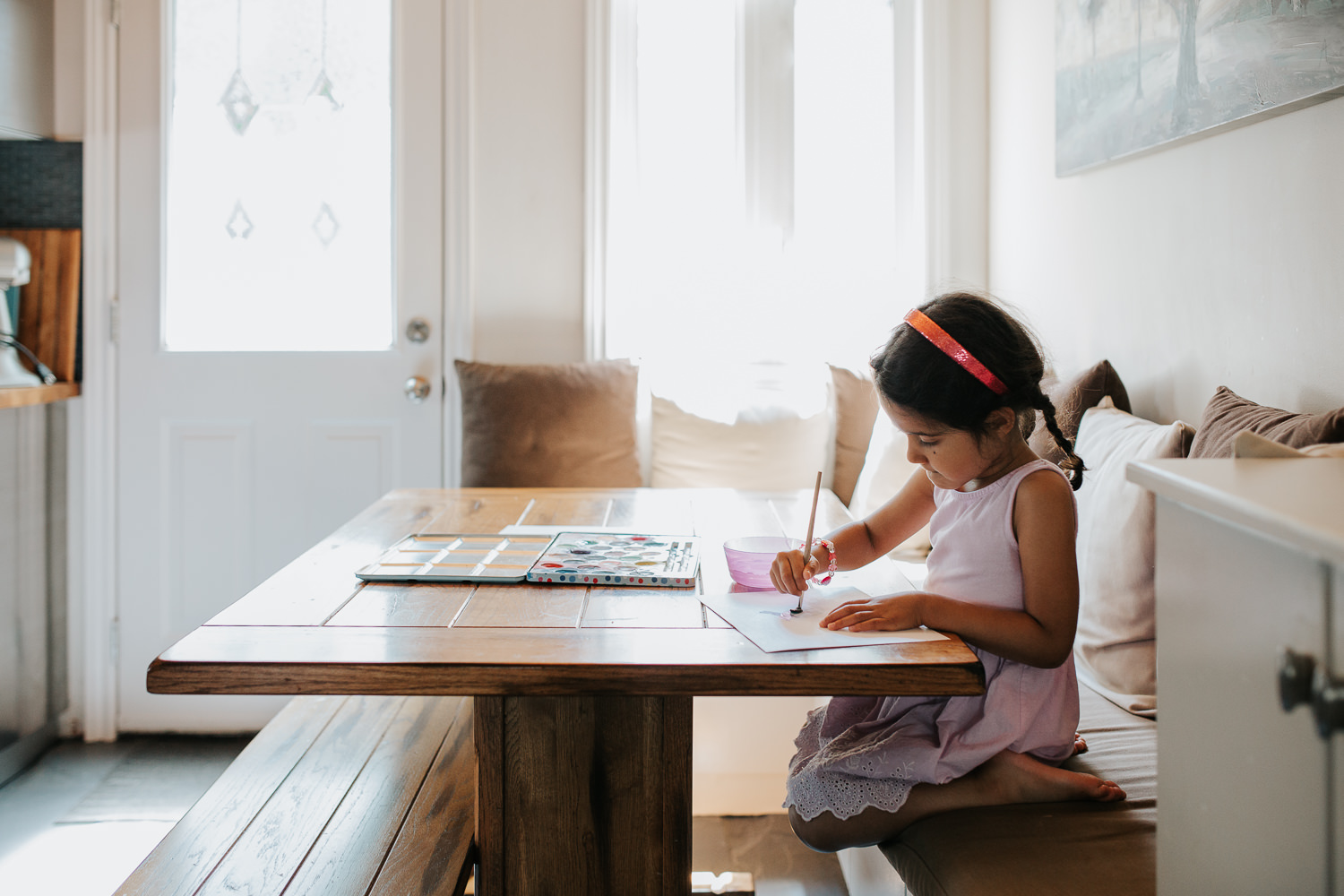 4 year old toddler girl with dark hair in pigtails wearing purple dress sitting at kitchen table painting with watercolours - Newmarket Lifestyle Photos