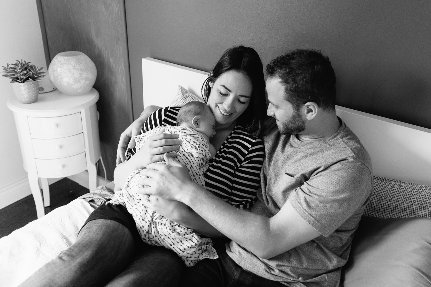 family of 3, new parents cuddle on bed, mom holding 2 week old baby girl covered with black and white swaddle, dad embracing wife and daughter - Uxbridge Lifestyle Photography