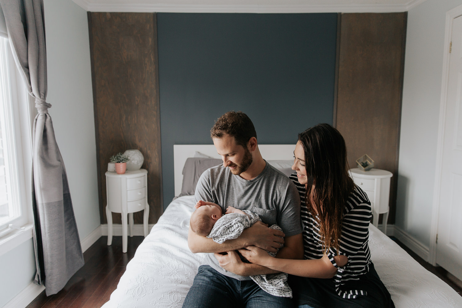 family of 3, new parents sitting on the edge of bed, dad holding 2 week old baby girl with light hair, mom snuggled next to husband, smiling at daughter - York Region In-Home Photography