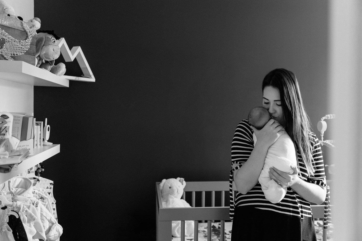 new mom standing in nursery in front of crib holding 2 week old sleeping baby girl wrapped in white swaddle to her chest, mother's eyes closed - Markham Lifestyle Photos