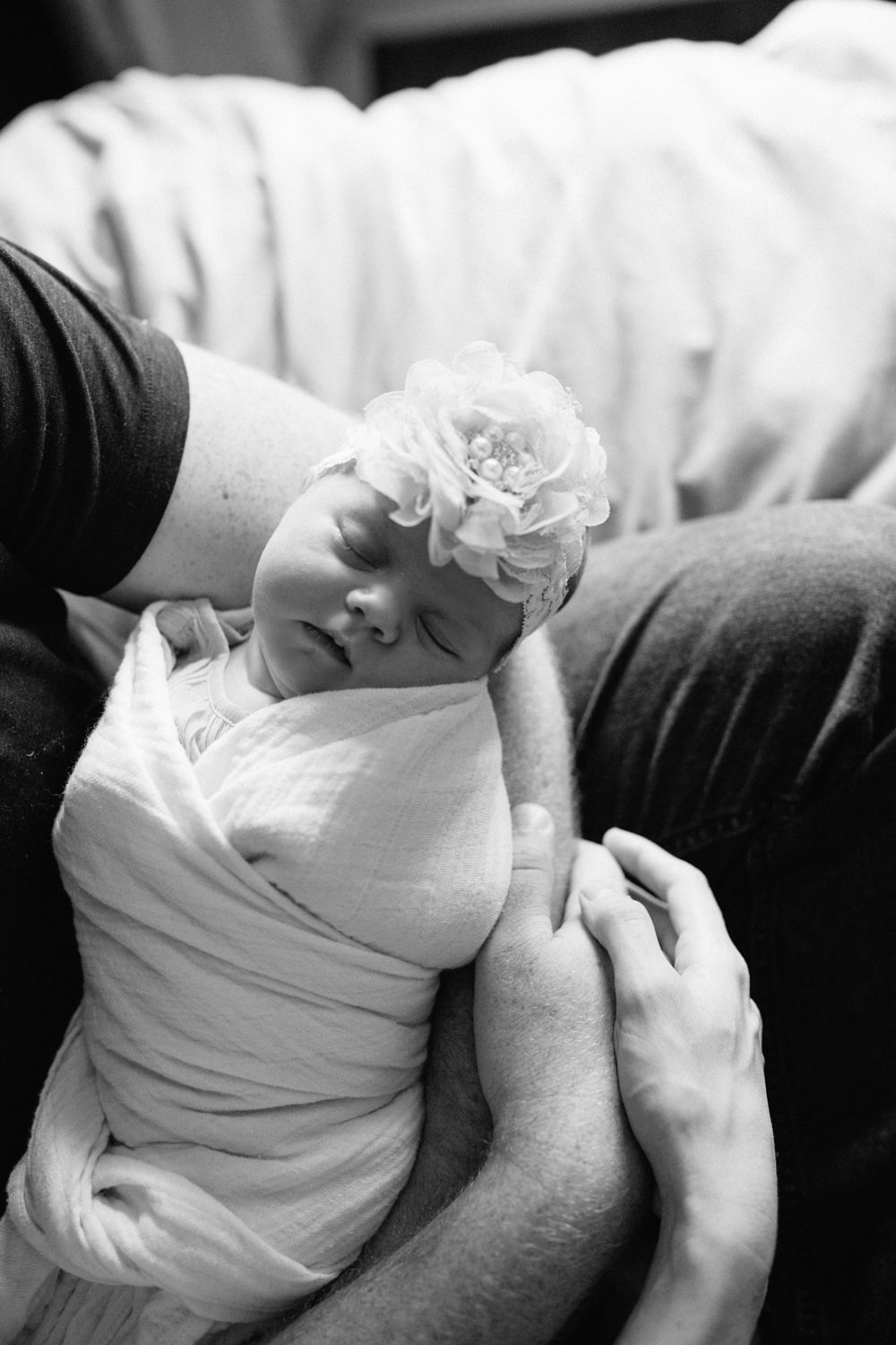 2 week old baby girl with flower headband on lying asleep in white swaddle in father's arms, mom's hand on dad's - Barrie In-Home Photography