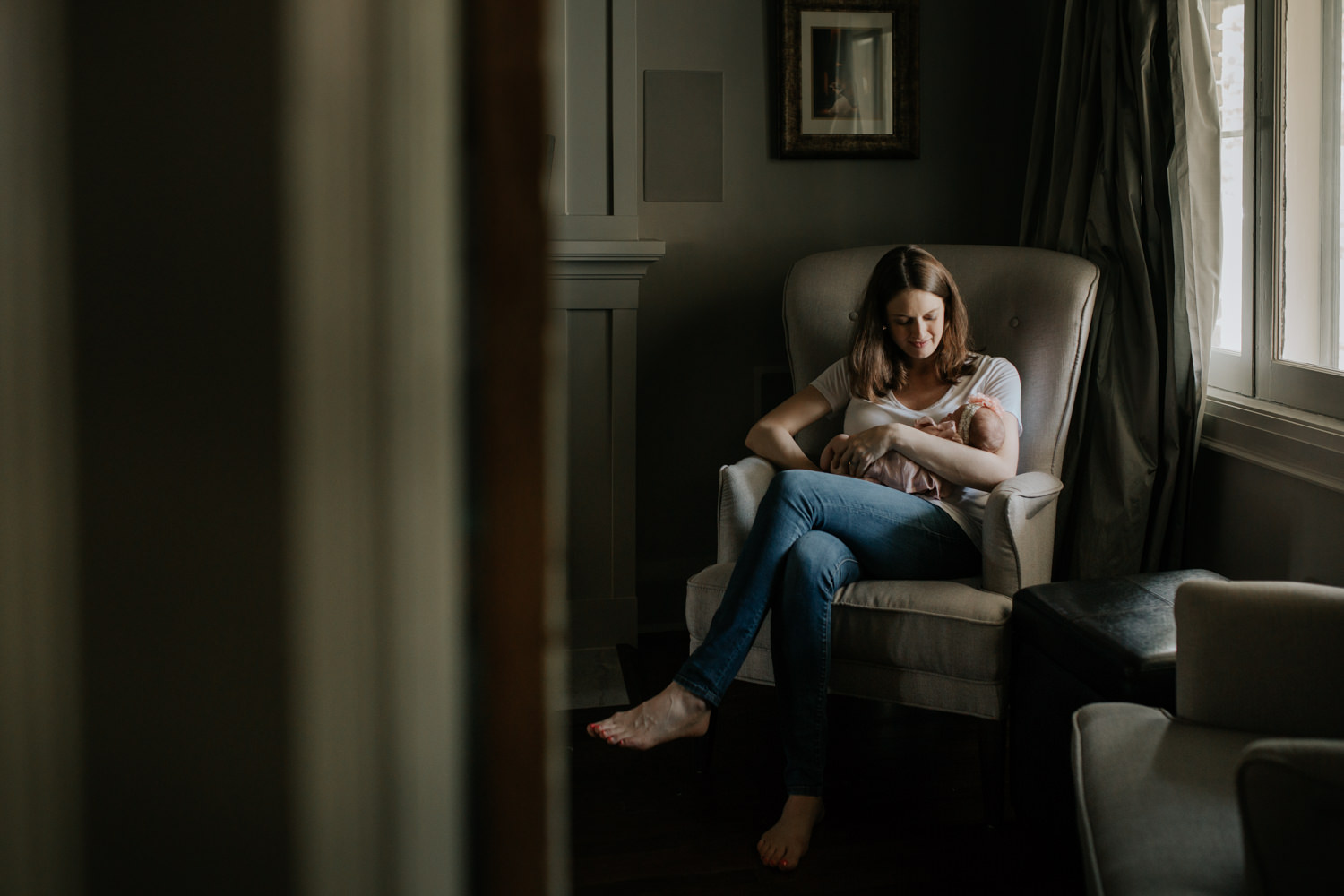 new mother wearing white t-shirt and jeans sitting on chair in living room, holding and looking at 2 week old baby girl in her arms - Barrie Lifestyle Photos