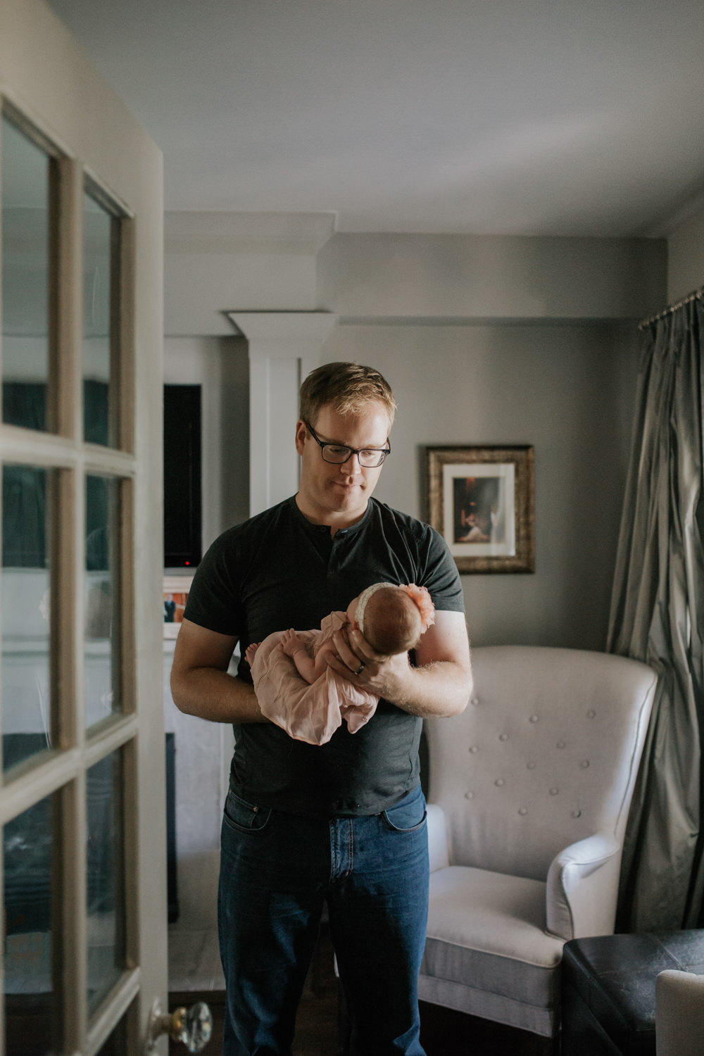first time dad standing in living room holding 2 week old baby girl in blush dress and flower headband, smiling at daughter - York Region Lifestyle Photos