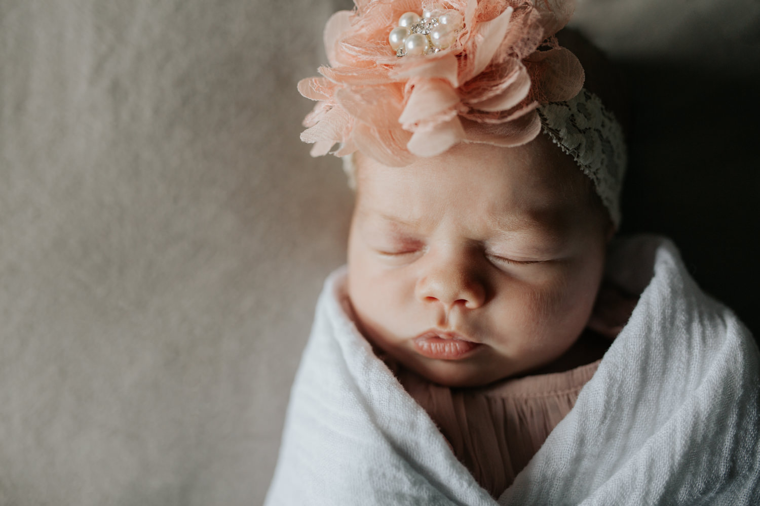 2 week old baby girl wrapped in white swaddle wearing pink flower headband fast asleep lying on master bed, lips pursed - Markham Lifestyle Photography