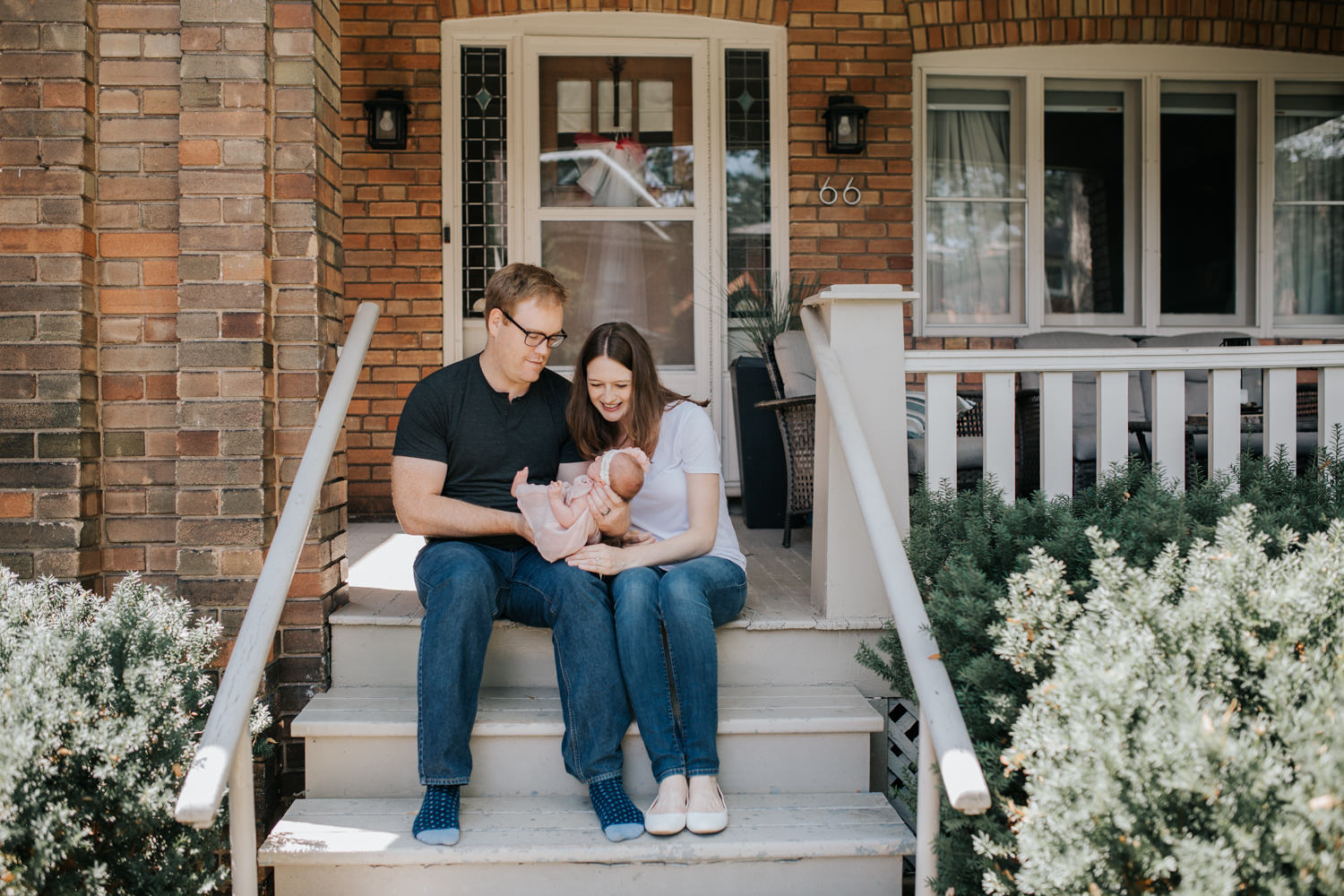 family of 3 sitting on front porch on summer day, dad holding 2 week old baby girl, mom leaning in next to husband smiling at daughter - GTA Lifestyle Photography
