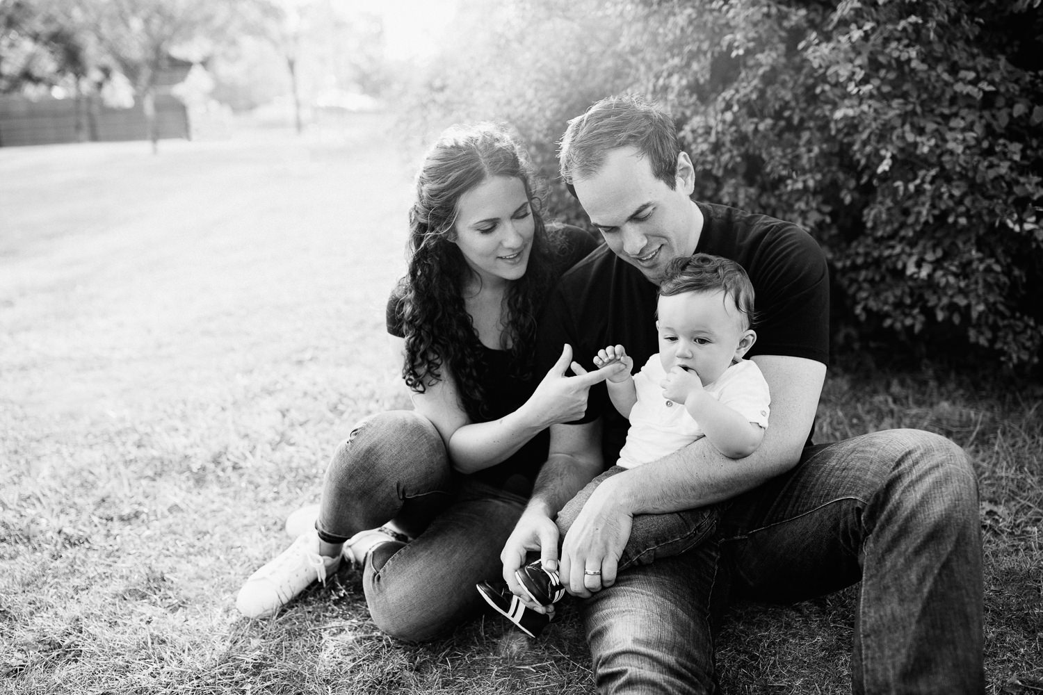 family of 3 sitting on ground in park, 9 month old baby boy with dark hair sitting in dad's lap, mom snuggled next to them holding son's hand - Barrie Lifestyle Photography