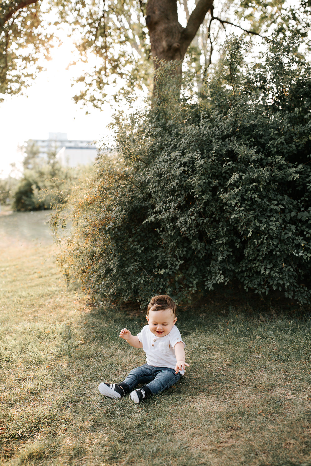 9 month old baby boy with dark hair in white t shirt, jeans and sneakers sitting on grass in park in front of greenery playing and smiling -  Markham Lifestyle Photos