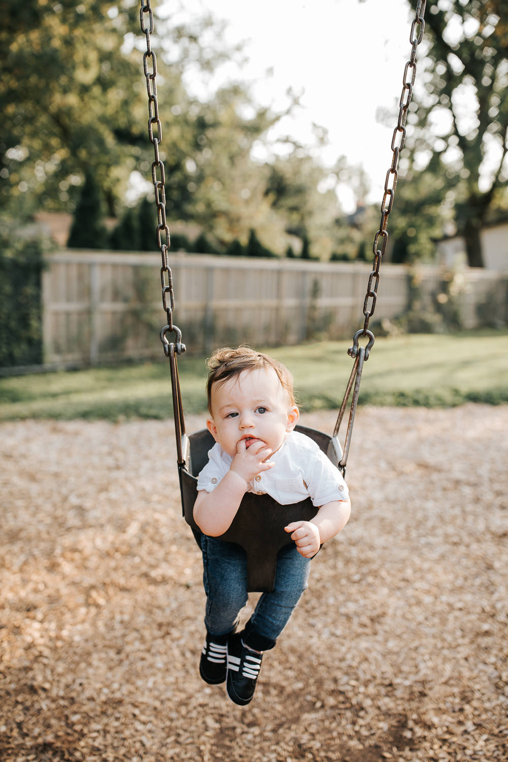 9 month old baby boy with dark brown hair wearing white t-shirt, jeans and sneakers with hand in mouth looking serious  as he sits in swing at park - Stouffville Golden Hour Photography