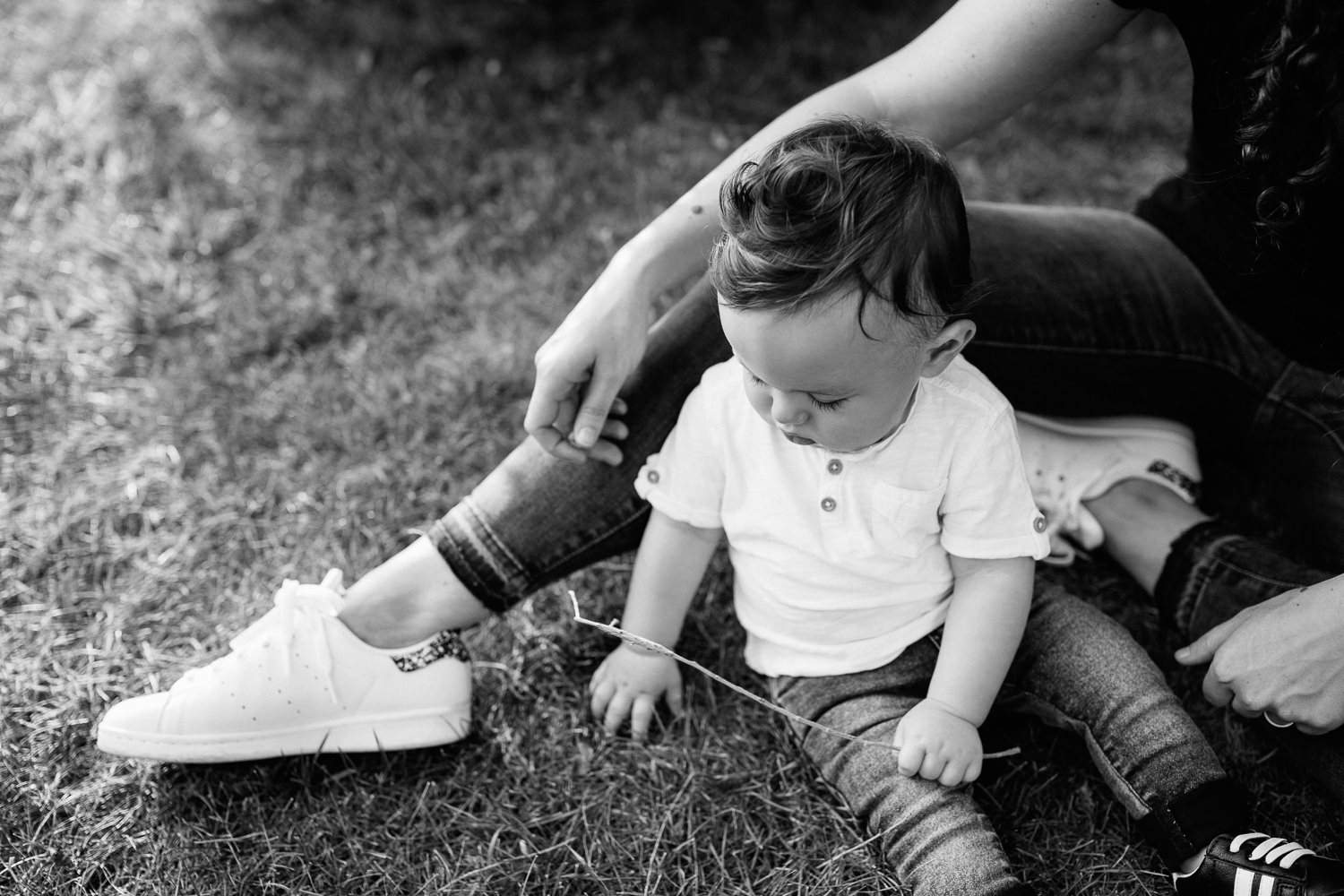 York9 month old baby boy with dark brown hair wearing white t-shirt, jeans and sneakers sitting on ground playing with grass at park, mom sitting next to son -  Region Golden Hour Photography