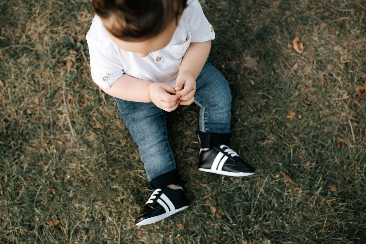 9 month old baby boy wearing white t-shirt, jeans and sneakers sitting on grass at park in front of greenery, close up of clasped hands and feet - GTA Golden Hour Photos