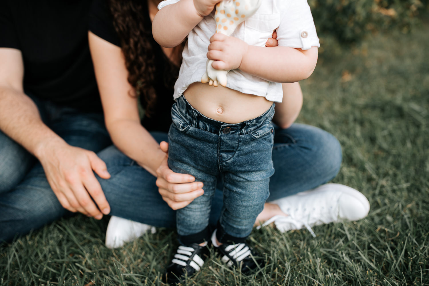 9 month old baby boy in white t-shirt, jeans and sneakers standing holding Sophie the giraffe, mom and dad sitting behind son, close up of bellybutton - Newmarket Lifestyle Photography