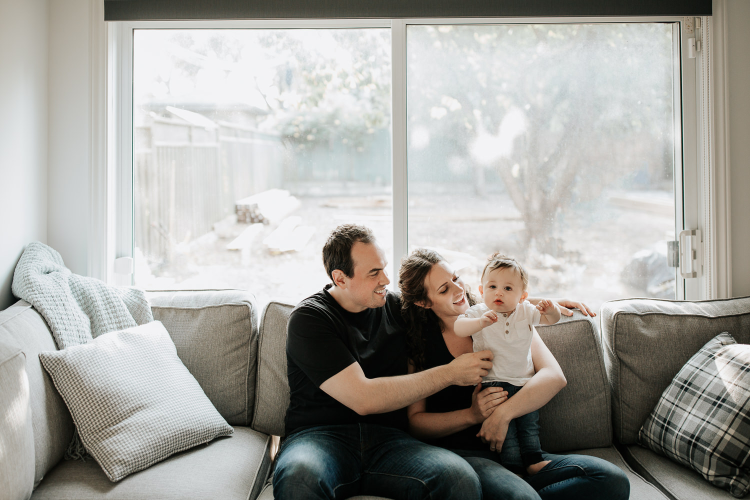 family of 3 sitting on couch, 9 month old baby boy with dark hair standing on mom's lap looking at camera, parents smiling at son - Stouffville Golden Hour Photography