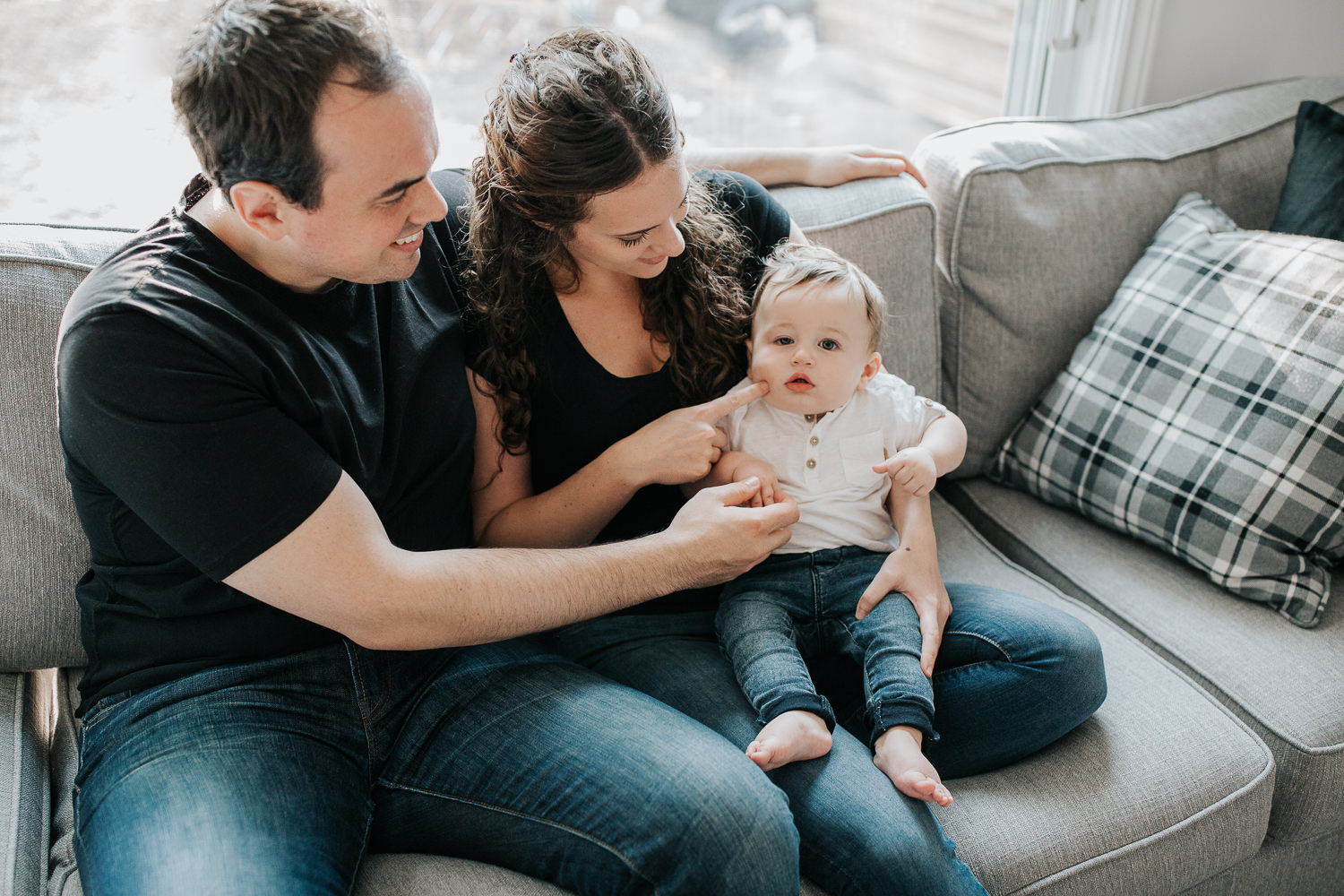 family of 3 sitting on couch, 9 month old baby boy with dark hair sitting on mom's lap looking at camera, parents smiling at son - Newmarket Golden Hour Photography