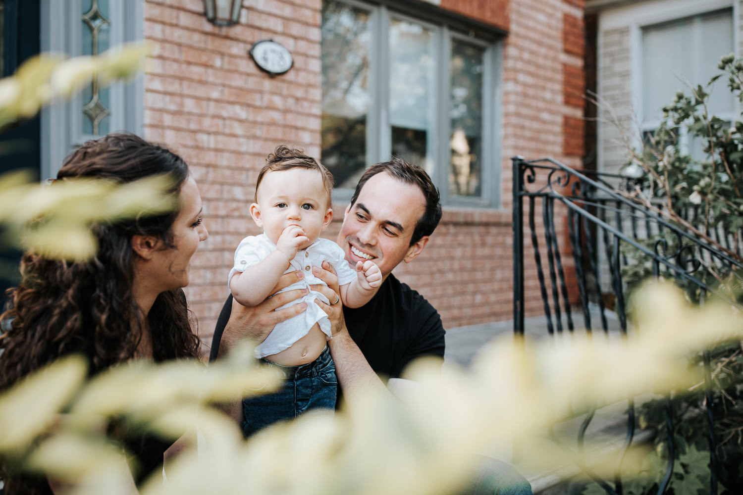 family of 3 sitting on front porch, 9 month old baby boy with dark hair in white t-shirt and jeans standing in dad's lap, mom smiling at son and husband - York Region Golden Hour Photography