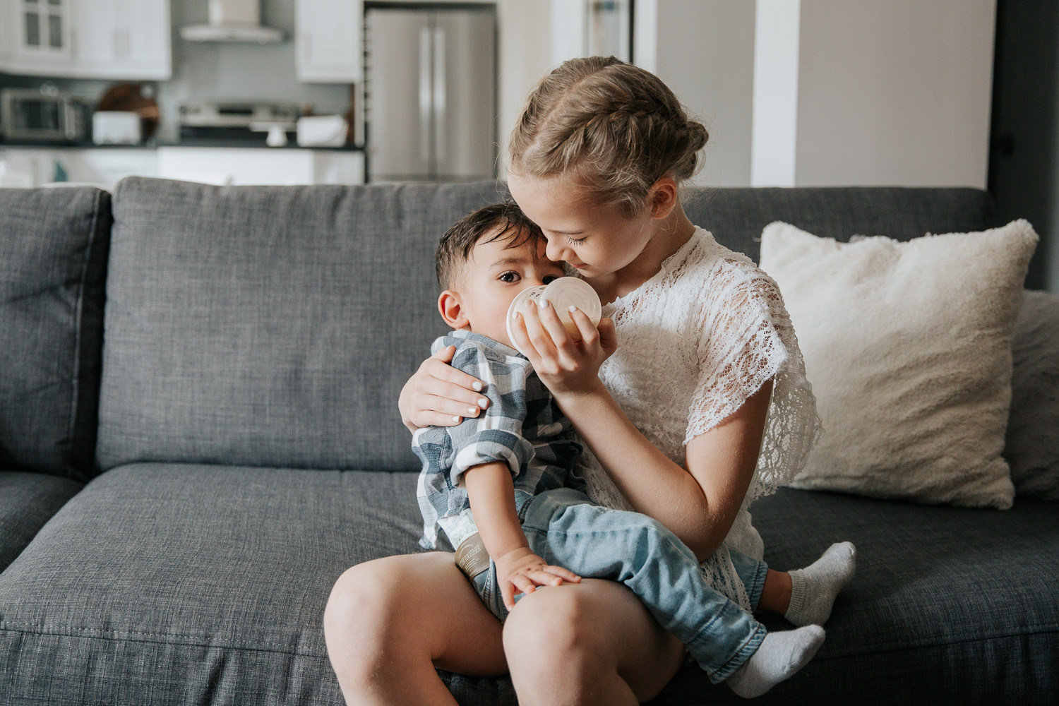 11 year old girl with blonde hair sitting on couch feeding 1 year old dark haired boy in shirt and jeans a bottle - Newmarket Lifestyle Photography