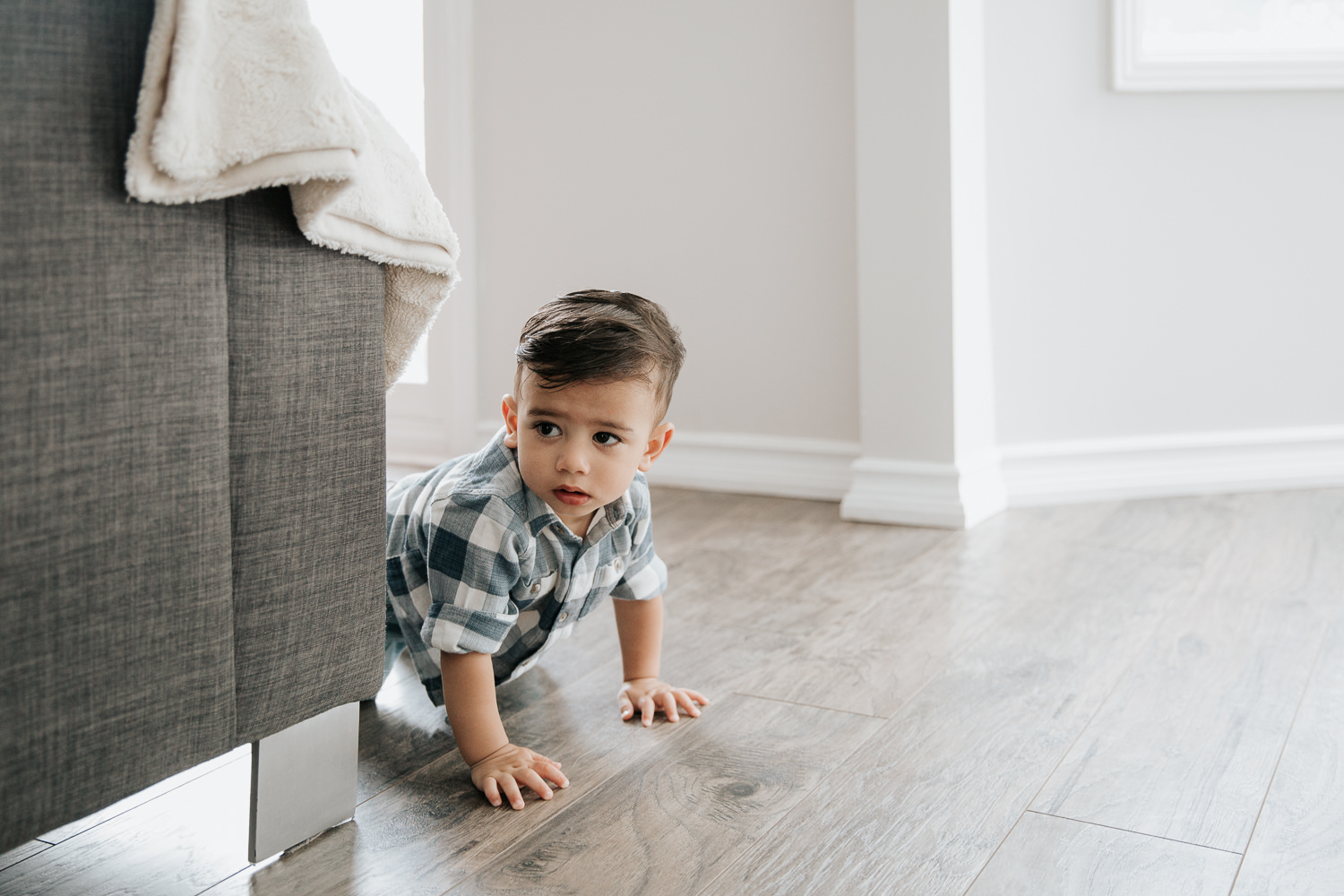 1 year old baby boy with dark hair and eyes in plaid blue and white button down shirt crawling on hardwood floor past couch - GTA Lifestyle Photography
