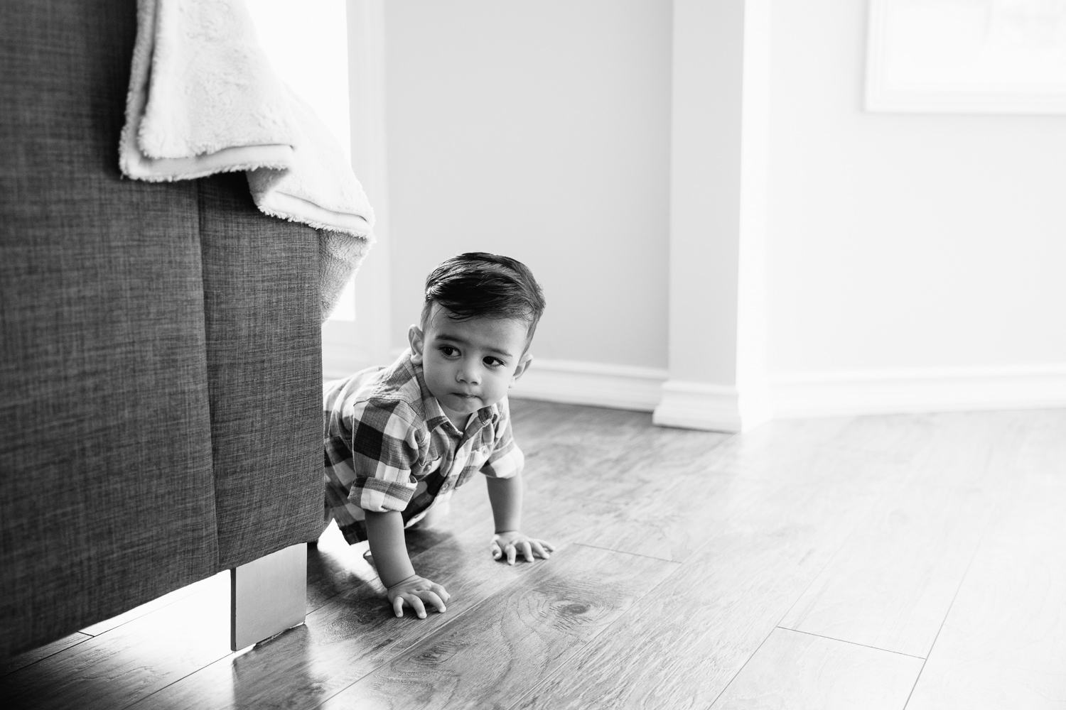 1 year old baby boy with dark hair and eyes in plaid button down shirt crawling on hardwood floor past couch - York Region Lifestyle Photography