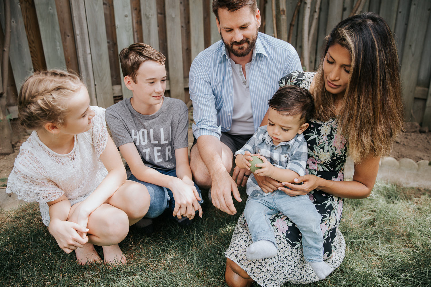 family of 5 in backyard sitting on grass, dad, brother and sister smiling at one year old baby boy sitting in mom' lap holding apple - Markham Lifestyle Photos
