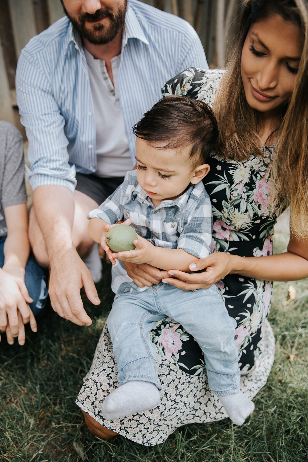 1 year old baby boy with dark hair in white and blue plaid shirt and jeans sitting in mom's lap holding an apple -Barrie Lifestyle Photos