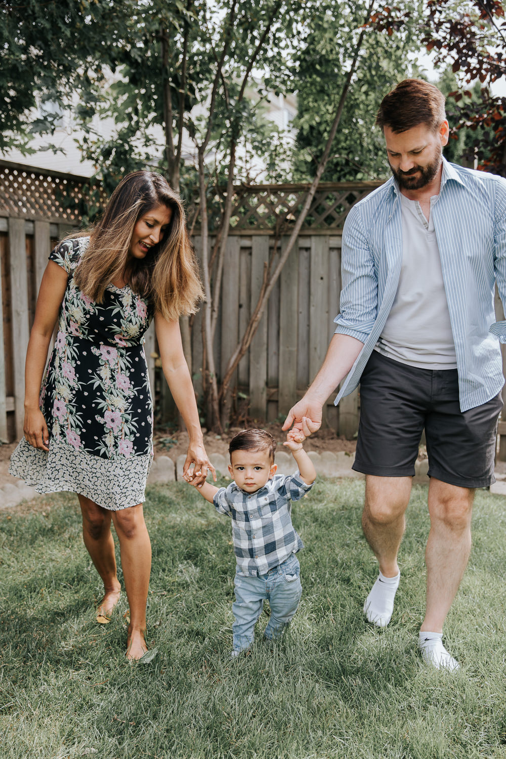 1 year old baby boy with dark hair in white and blue plaid shirt and jeans holding mom and dad's hands as parents help him walk between them in backyard -GTA Lifestyle Photos