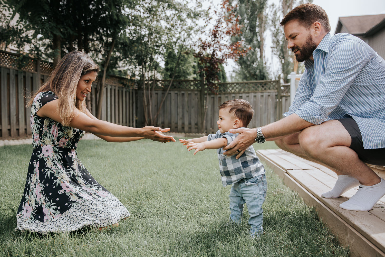 1 year old baby boy with dark hair in white and blue plaid shirt and jeans standing in backyard, supported by dad as mom and son reach out arms to one another, smiling -York Region Lifestyle Photos