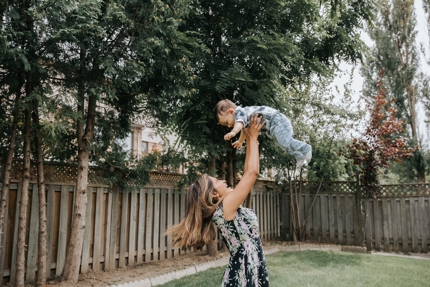 1 year old baby boy with dark hair in white and blue plaid shirt and jeans being thrown in air in backyard by mom - Newmarket Lifestyle Photography