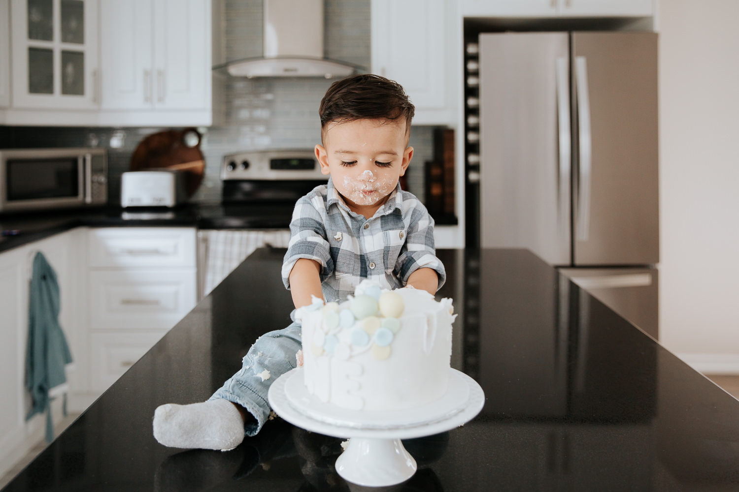 1 year old baby boy with dark hair sitting on kitchen counter eating cake for first birthday - Barrie In-Home Photos