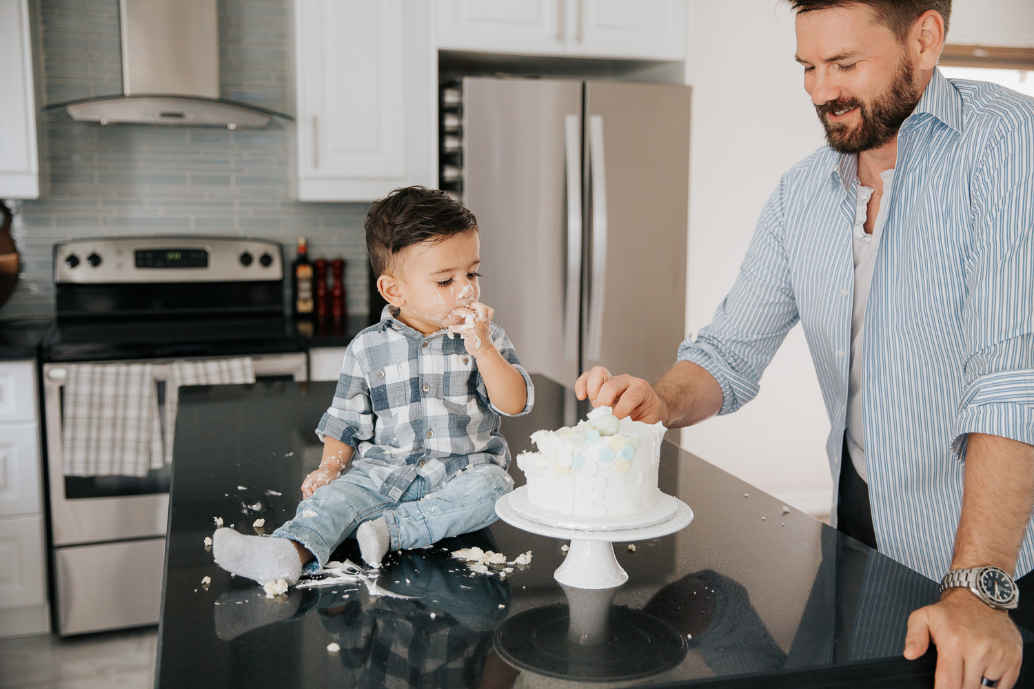 1 year old baby boy with dark brown hair and eyes in blue and white plaid shirt putting cake in his mouth and watching dad take piece - Newmarket In-Home Photography