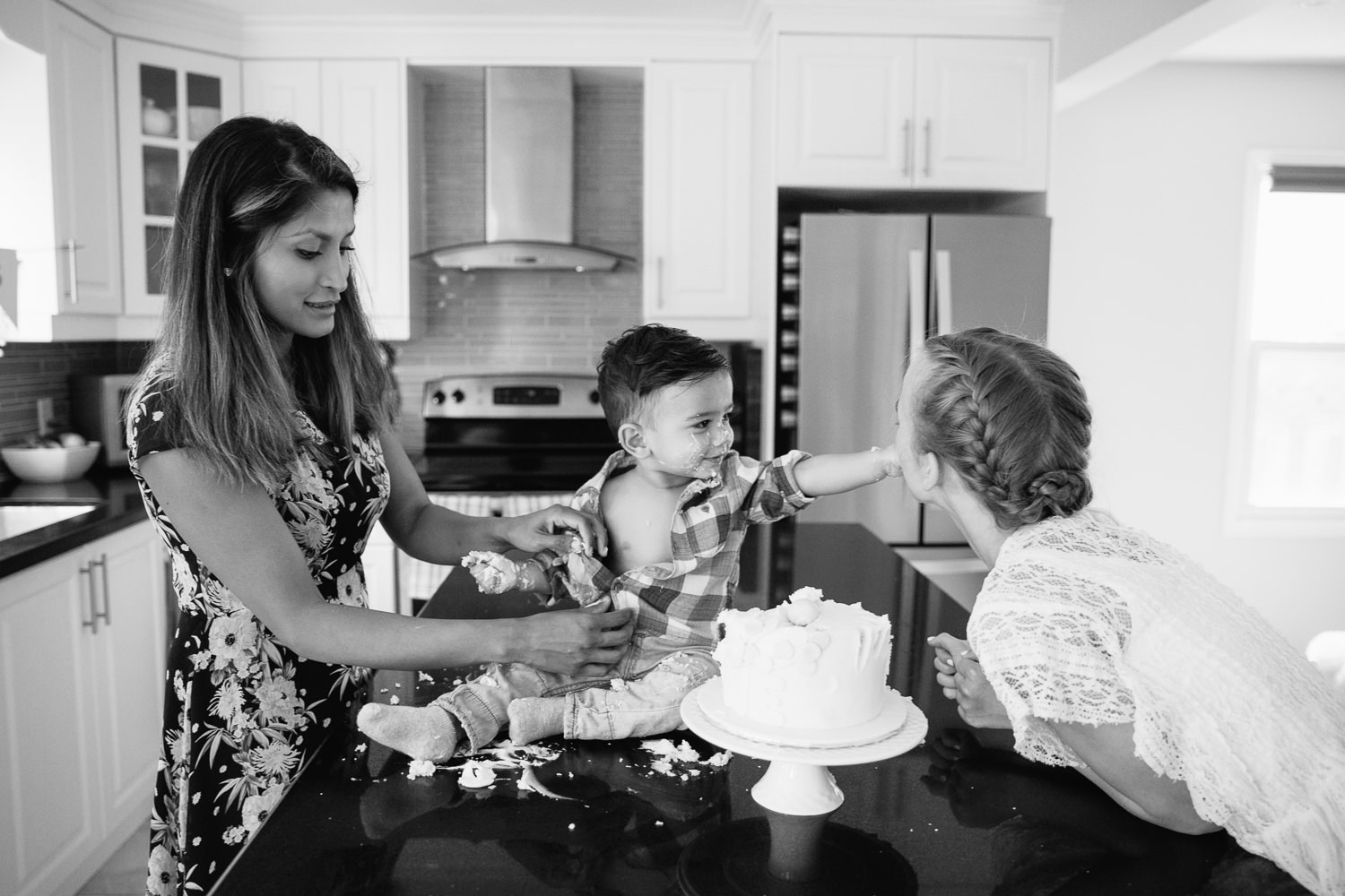 1 year old baby boy with dark brown hair and eyes in plaid shirt sitting on kitchen counter doing cake smash as mom takes off his shirt, son is feeding big sister - Markham In-Home Photography