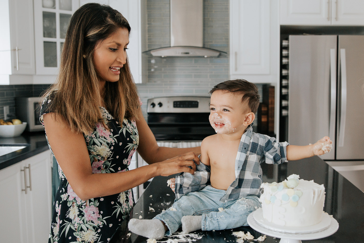1 year old baby boy with dark brown hair and eyes in blue and white plaid shirt sitting on kitchen counter doing cake smash as mom tries to take off his shirt - Barrie In-Home Photography