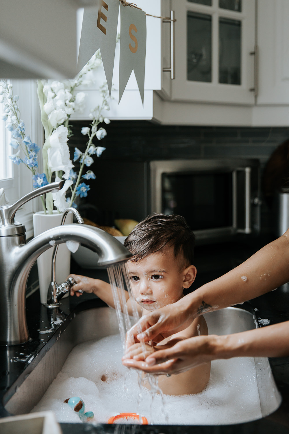 1 year old baby boy with dark hair and eyes sitting in kitchen sink getting bath, water running as mom holds son's hand under it - Newmarket Lifestyle Photography