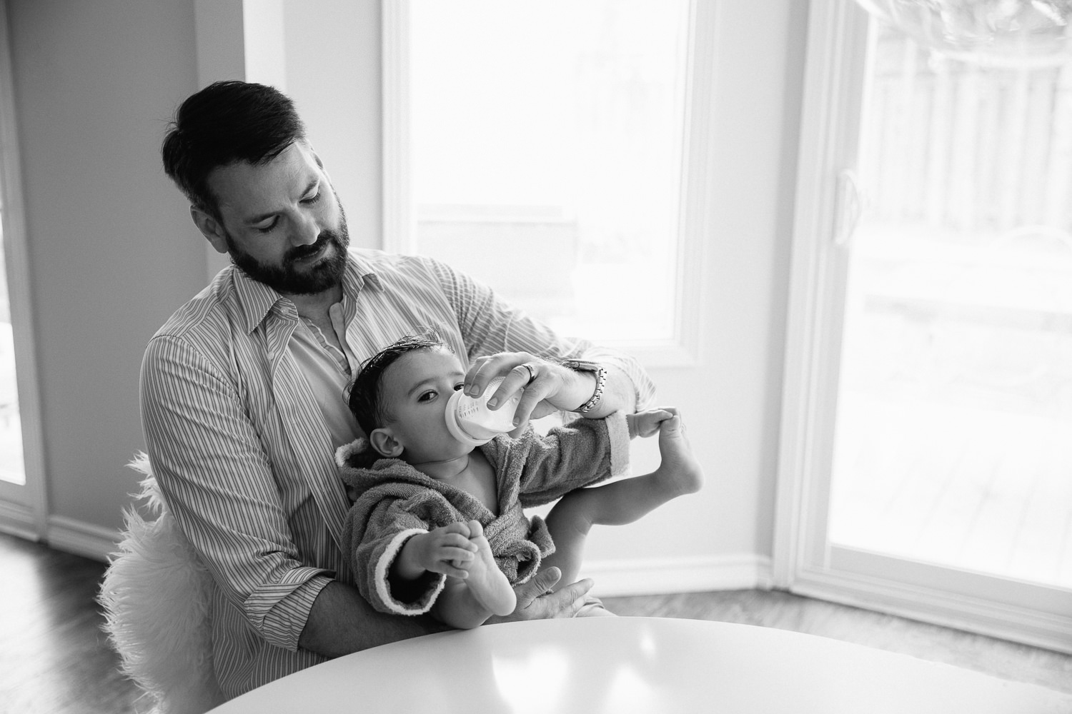 dad sitting at kitchen table holding 1 year old baby boy in hooded towel in his lap and feeding him bottle, son holding his feet as he eats - Newmarket In-Home Photos