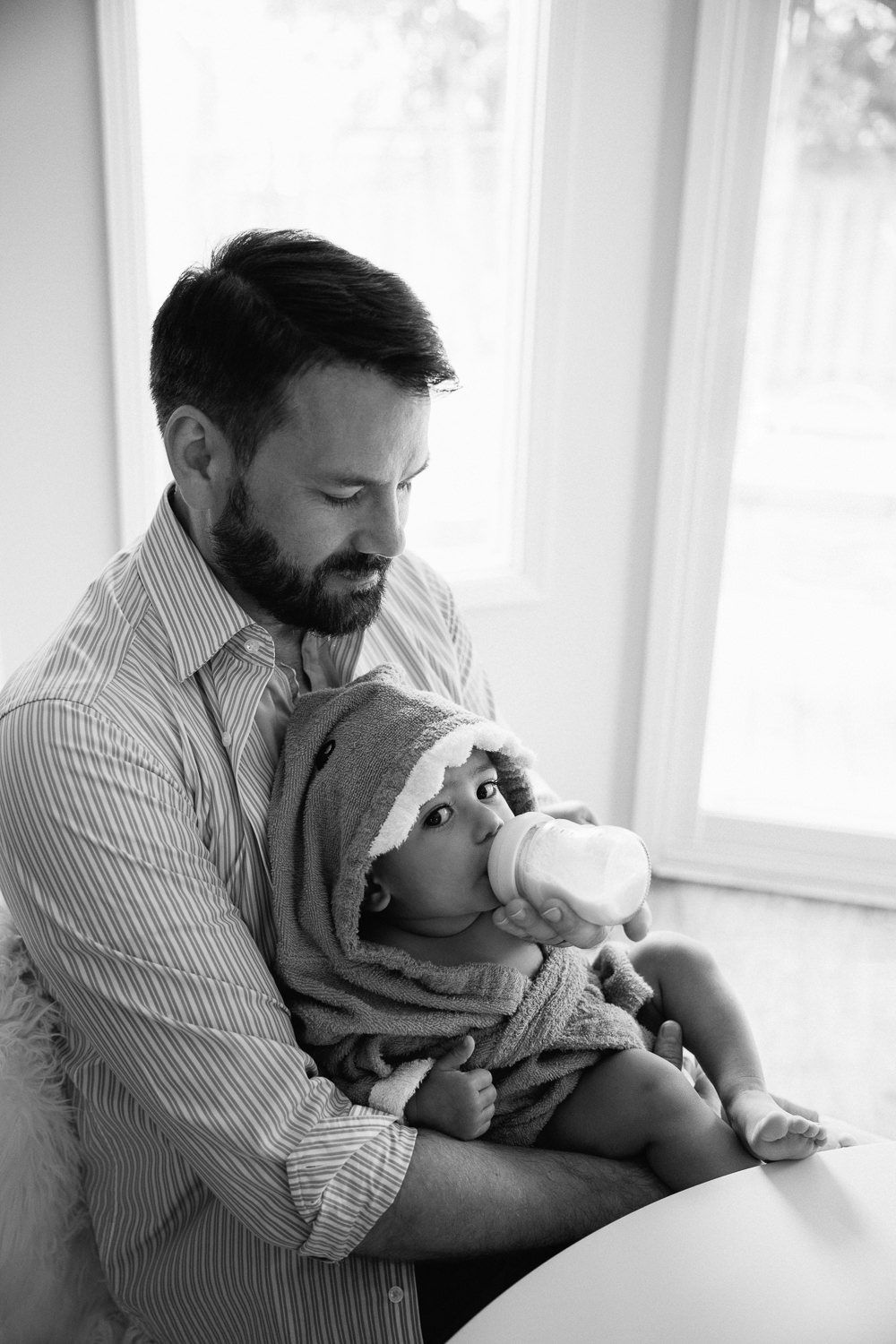 dad sitting at kitchen table holding 1 year old baby boy in hooded towel in his lap and feeding him bottle -Markham In-Home Photos