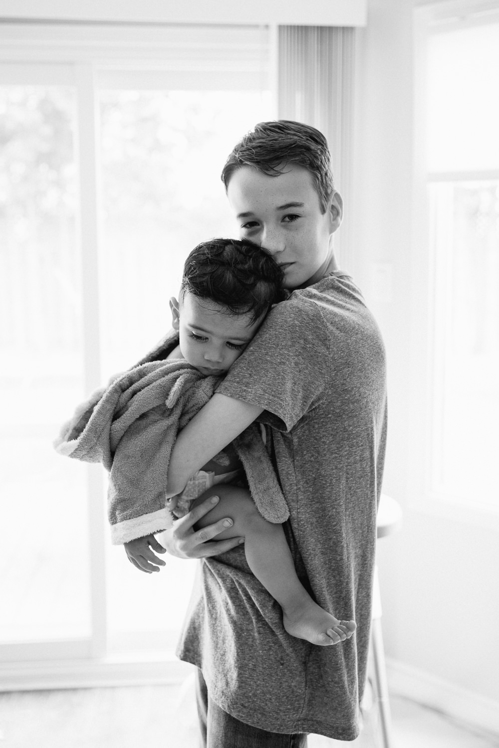 13 year old big brother standing in kitchen holding 1 year old baby boy wearing bath robe and resting head on his shoulder -Stouffville In-Home Photos