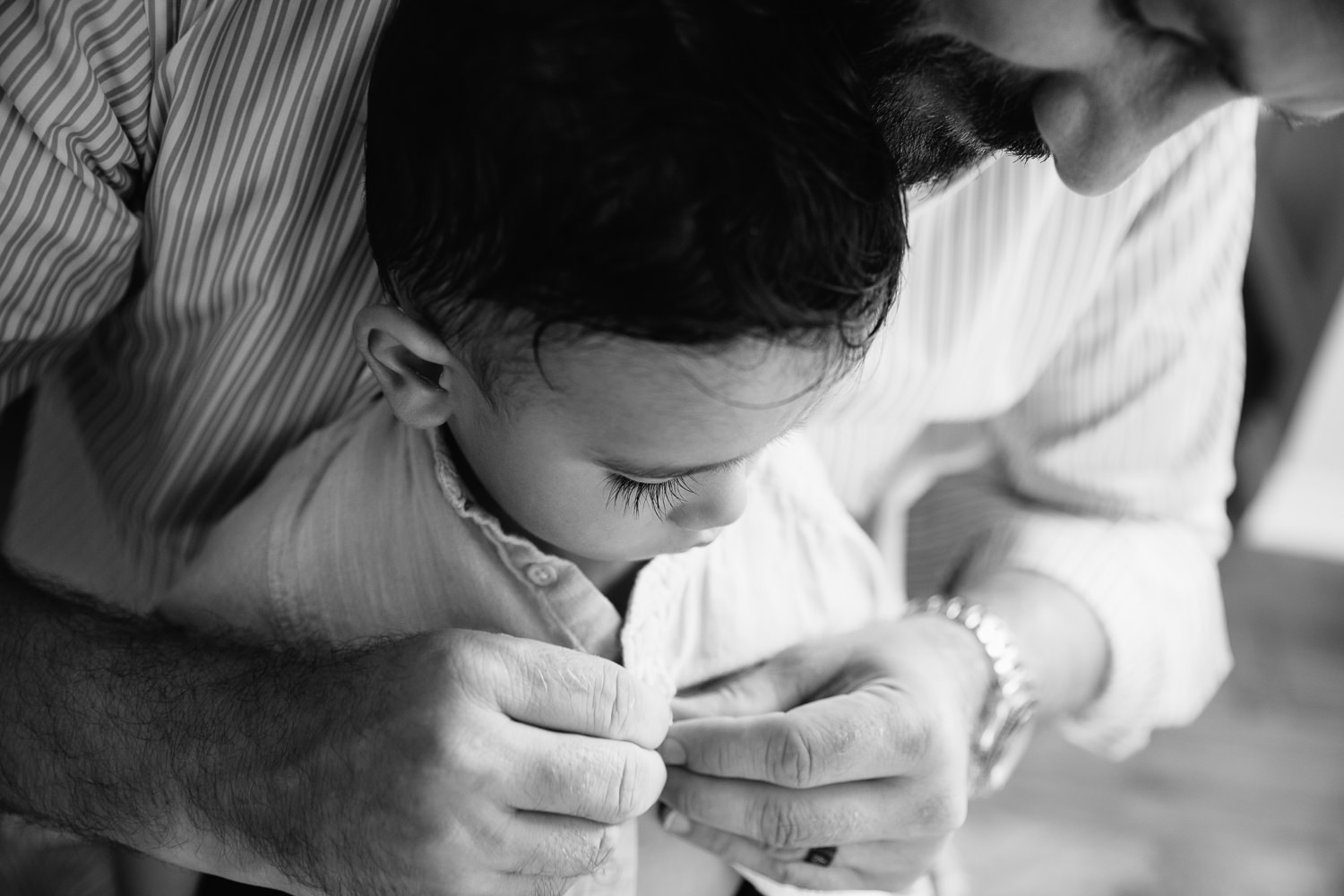 1 year old baby boy with dark hair and long eyelashes sitting in dad's lap as father button's son's shirt - Barrie In-Home Photos