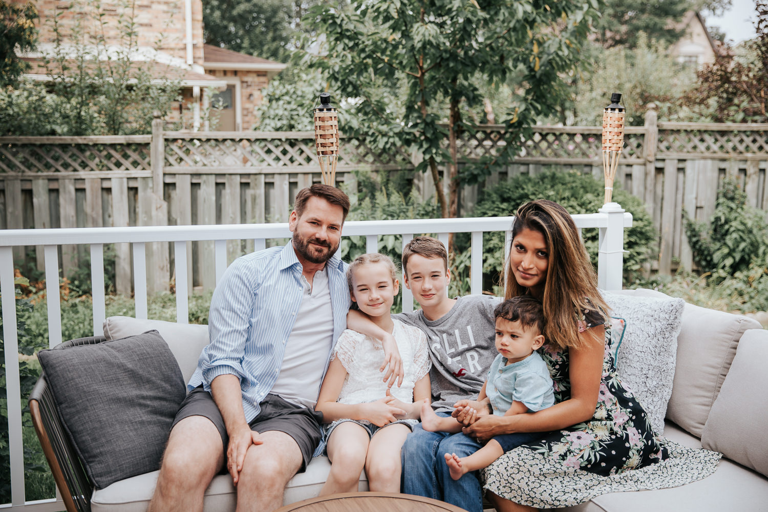 family of 5 sitting on couch on backyard deck, 11 year old girl, 13 year old boy and 1 year old baby sitting between parents, smiling at camera - Markham Lifestyle Photography