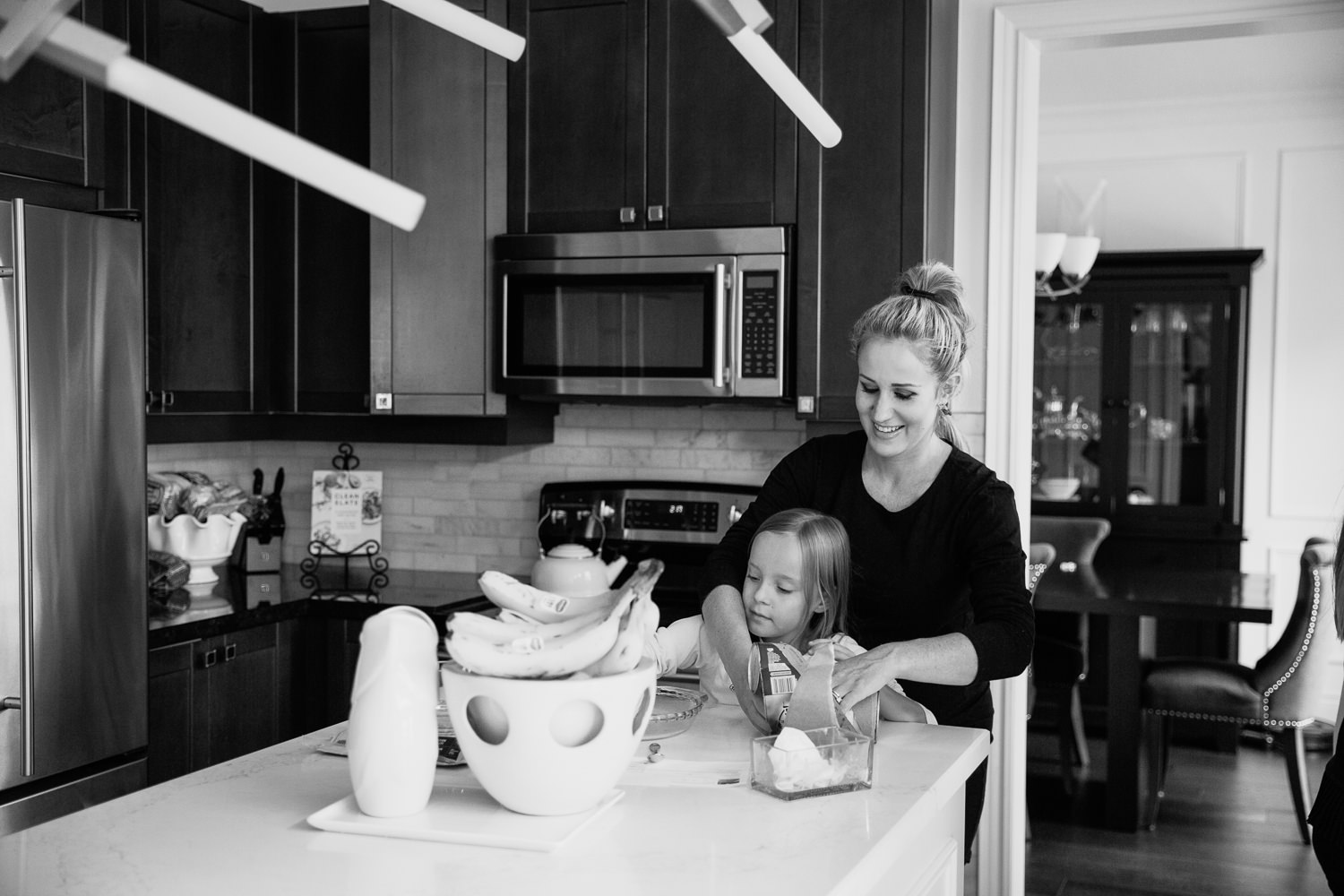 mom and 8 year old girl standing at kitchen island together, mother with arms around daughter preparing food - Barrie In-Home Photos