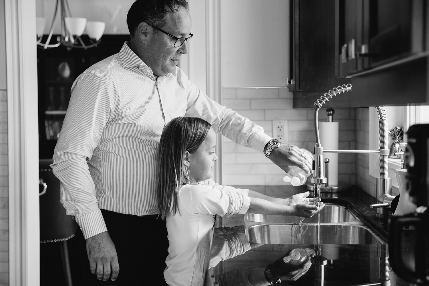 father and 8 year old daughter standing at kitchen sink, dad pouring dish soap into girl's outstretched hands - Markham In-Home Photos